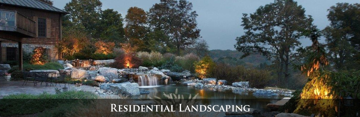 Residential patio adjacent to a pond and waterfall with low voltage landscape lighting